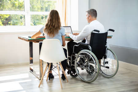 Disabled Businessman Sitting With His Partner With Laptop Over Desk In Office