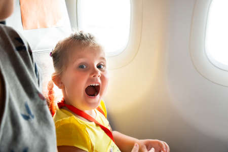 Little Girl Sitting Next To Mother Screaming On Airplane