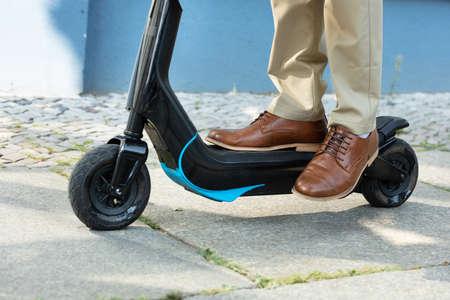 Giovane uomo in sella a uno scooter elettrico