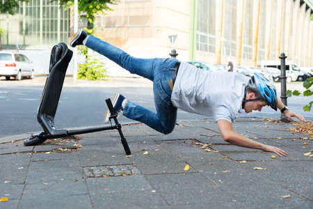 Man Having Accident Falling From E-Scooter On Street Stock Photo