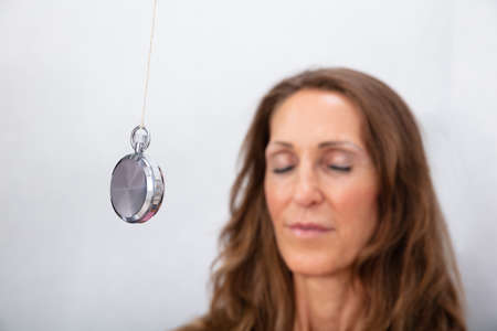 Aantrekkelijke rijpe vrouw wordt thuis gehypnotiseerd met slinger