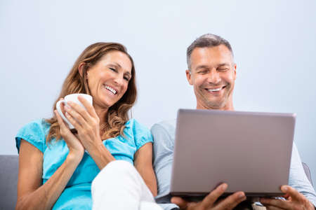Happy Mature Couple Sitting On Sofa Watching Movie In Laptop At Home