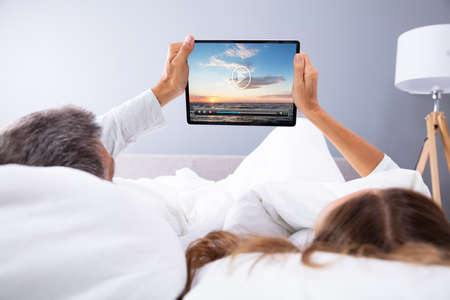 Couple Watching Movie On Digital Tablet While Lying In Bed Archivio Fotografico