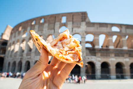 Hand Holding Slice Of Italian Pizza Near Colosseum, Rome