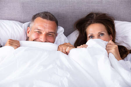 High Angle View Of An Couple Trying To Hide In Blanket