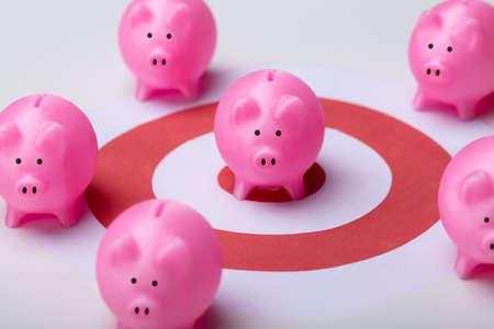 Pink Piggy Banks On Darts Target Surrounded With Other Piggy Banks Over White Desk Reklamní fotografie