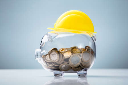 Close-up Of Yellow Hard Hat Over Transparent Piggy Bank On White Desk Against Blue Background