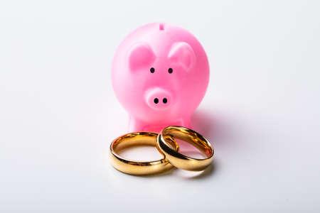 Nahaufnahme der goldenen Eheringe mit rosa Sparschwein angeordnet über isoliert auf weißem Hintergrund Standard-Bild