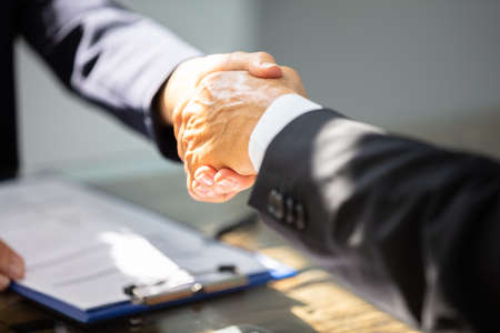 Close-up Of Businesspersons Hand Shaking With Partner