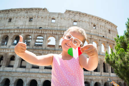 Girl Wearing Italian Flag Sunglasses, Holding Heart And Showing Thumb Up Near Colosseum, Rome, Italy Stock fotó