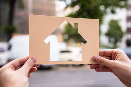 Hands Holding Paper With Cutout House Outdoors