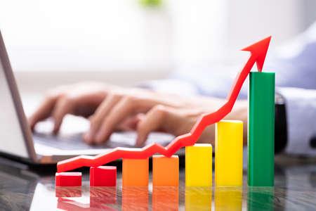 Growth Chart Near Man Working On Laptop
