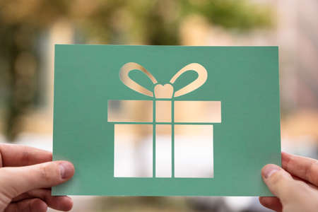 Hands Holding Paper With Cutout Gift Outdoors Stockfoto