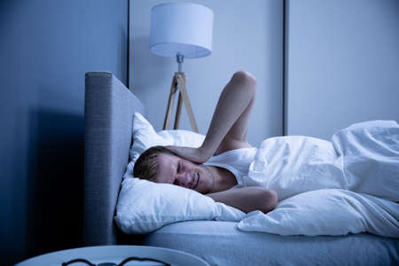 Man Covering His Head With Pillow In Bed