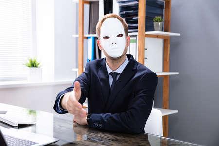 Sleazy Young Salesman Offering Handshake In Office 写真素材
