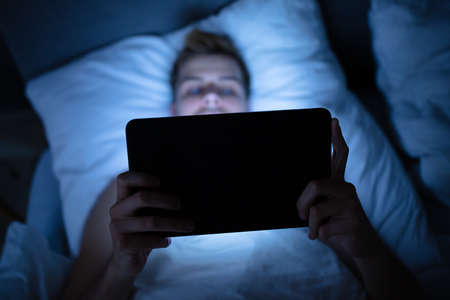 Man In Bed With Digital Tablet At Night