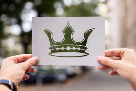 Hands Holding Paper With Cutout Crown Outdoors
