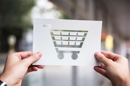 Hands Holding Paper With Cutout Shopping Cart Outdoors