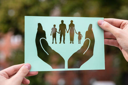 Hands Holding Paper With Cutout Hands Protecting Family Outdoors Stockfoto