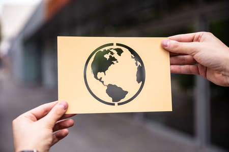 Hands Holding Paper With Cutout Planet Earth Outdoors