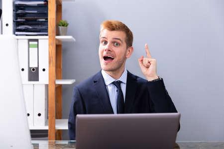 Geschäftsmann mit Ah-Ha-Moment während der Arbeit im Büro auf Laptop Standard-Bild