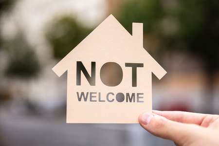 Hands Holding Paper With Cutout House And Non Welcome Words Bicycle Outdoors
