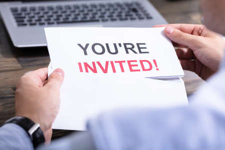 Man Opening White Envelope With You Are Invited Text