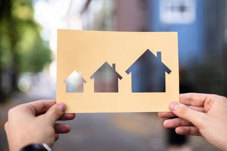 Mani che tengono la carta con la crescita della casa di ritaglio all'aperto