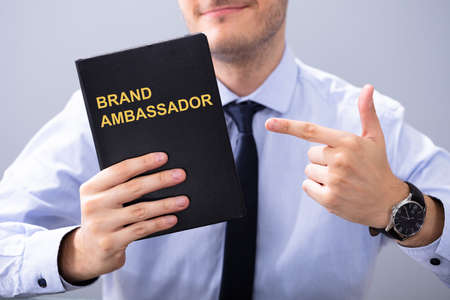 Man Holding Book With Brand Ambassador Text And Pointing