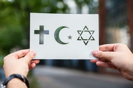 Hands Holding Paper With Cutout Religion Symbols Outdoors Stockfoto