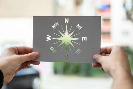 Hands Holding Paper With Cutout Compass Outdoors