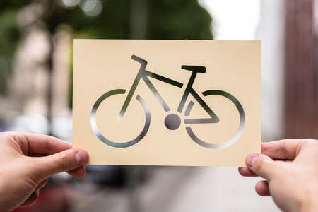 Hands Holding Paper With Cutout Bicycle Outdoors