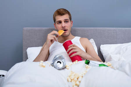 Man Eating In Messy Bed At Home