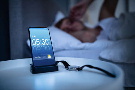 Man Waking Up With Alarm On Mobile Phone At Home