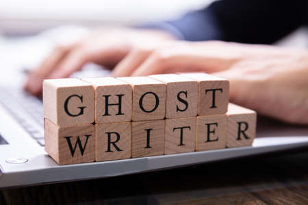 Ghostwriter Wooden Block On Computer Keyboard While Someone Typing