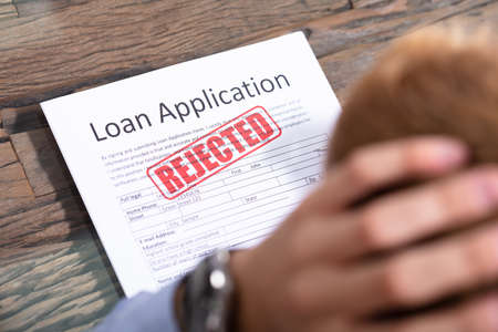 Stressed Person Looking At Rejected Loan Application 스톡 콘텐츠