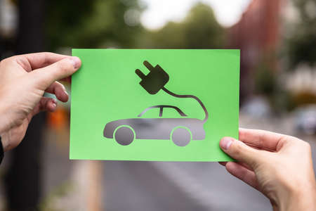 Hands Holding Paper With Cutout  Electric Car Outdoors