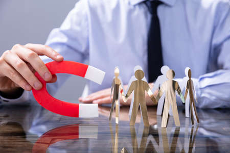 Businessperson Attracting Human Figures With Horseshoe Magnet