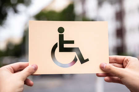 Hands Holding Paper With Cutout Disabled Sign Outdoors Stockfoto