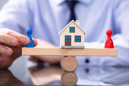 Scheidung Konzept. Abteilung für Hauseigentum. Männliche und weibliche Bauernfiguren auf Wippe Standard-Bild