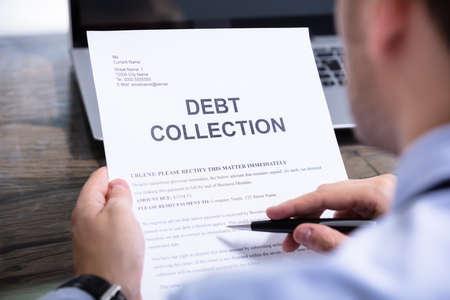 Hombre leyendo una carta de aviso de cobro de deudas en el escritorio Foto de archivo