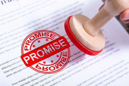 Businessman Hand Putting Promise Stamp On Document