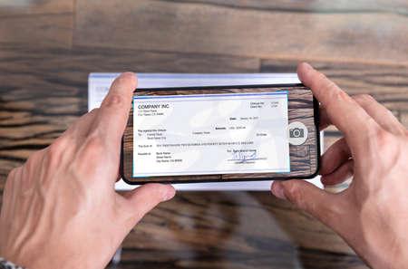 Mann, der ein Foto des Schecks macht, um eine Remote-Einzahlung bei der Bank vorzunehmen Standard-Bild