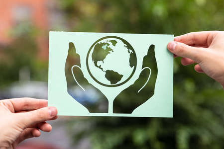 Hands Holding Paper With Cutout Hands Protecting Earth Outdoors