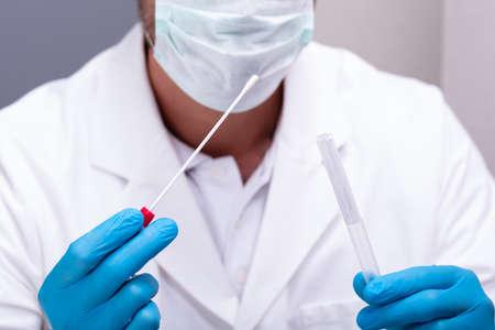 Médico varón con guantes azules sosteniendo hisopo de algodón y tubo de ensayo de ADN