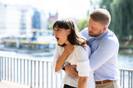 Man Helping Choking Woman To Expel A Trapped Object From Airway. Heimlich Maneuver 免版税图像