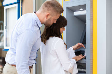 Man Spying For PIN Code While Woman Using ATM Machine For Withdrawing Money Stock fotó
