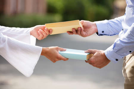 Close-up Of Couple's Hand Exchanging The Yellow And Blue Books At Outdoors