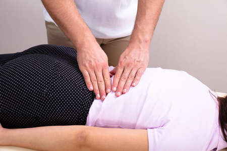A Male Physiotherapist Giving Back Massage To A Female Patient In The Clinic