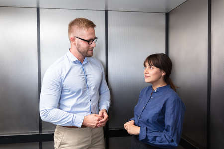 Side View Of A Businessman And Businesswoman Standing In Elevator Talking With Each Other
